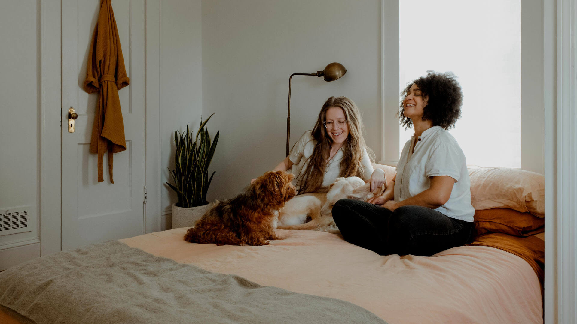 two women sitting on bed with dog